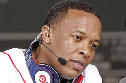 Dr. Dre takes in a baseball game, wearing both his headphones and a phone earpiece.