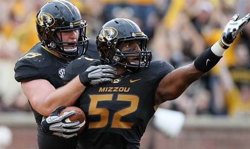 Michael Sam, right, celebrates with the football.